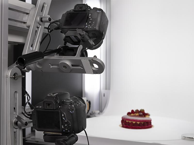 zoom sur deux appareils photo fixés sur le bras pour photographier un gâteau sous plusieurs angles